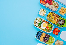 Plastic Lunch Boxes Filled With Healthy Food On Blue Background With Copy Space