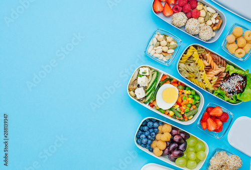 Plastic lunch boxes filled with healthy food on blue background with copy space Wallpaper Mural