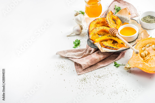 Autumn vegetarian food recipe. Organic roasted vegetables, Baked fried Hokkaido pumpkin with olive oil, herbs, garlic and honey. On a white stone background, copy space