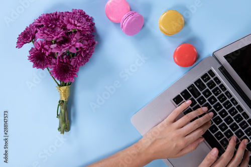 Woman tapping on her laptop with a blue background