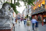 Fototapeta Londyn - Lisle Street In London Chinatown UK With Motion Blurred Tourists