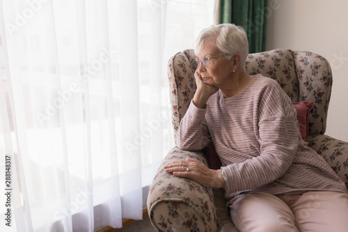 Cuadros en Lienzo  Front view of senior woman sitting on the couch and looking outside through wind