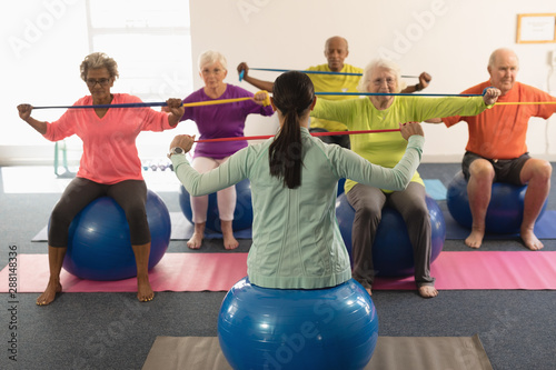 Young female trainer and senior people exercising with resistance band Wallpaper Mural