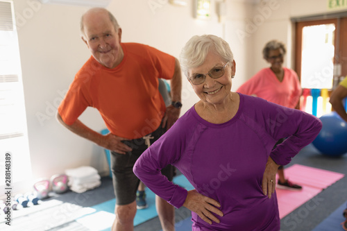 Front view of senior couple exercising in fitness studio