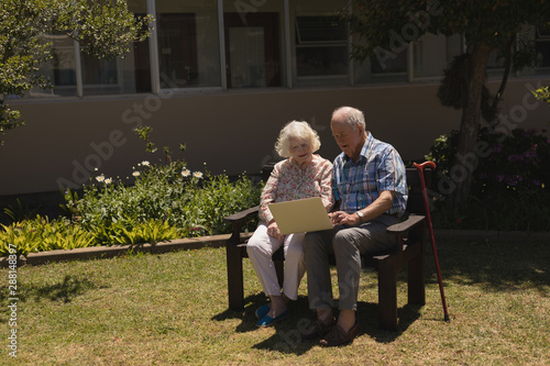 Front view of senior couple using laptop in garden