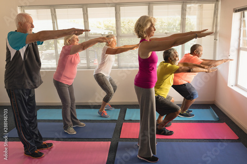 Group of senior people performing exercise at home