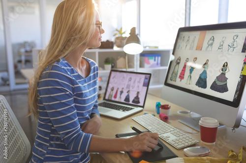 Obraz na plátně  Female fashion designer using graphic tablet while working at desk