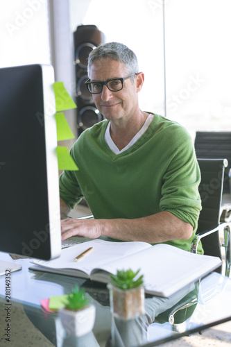 Happy businessman working on computer at desk in office