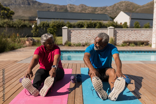 Senior couple performing stretching exercise in the backyard of home