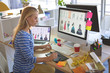 Female fashion designer using graphic tablet while working at desk