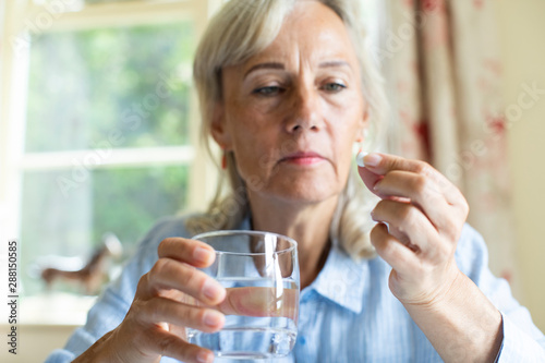 Senior Woman Taking Tablet With Glass Of Water At Home