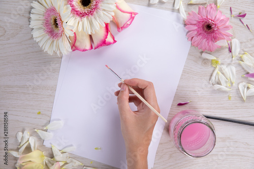 Woman painting a new sheet with some pink watercolor