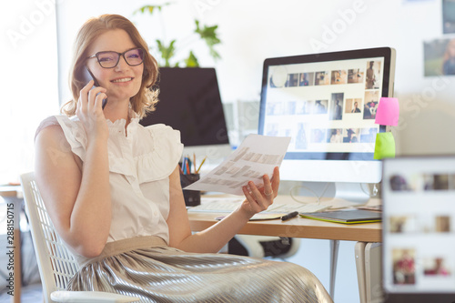 Female graphic designer talking on mobile phone in office