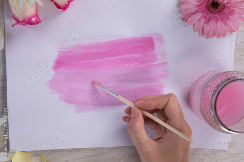Hand of a woman painting a watercolor on a flower and wooden background