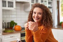 Smiling Young Woman Drinking Hot Tea In The Kitchen