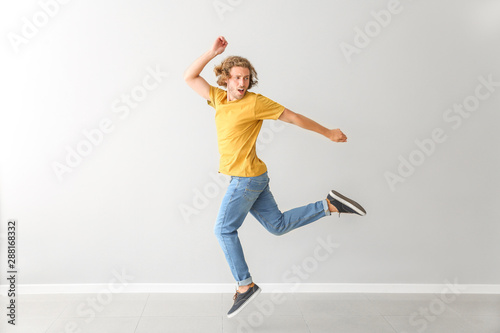 Handsome young man dancing against white wall
