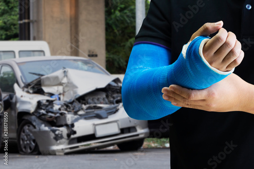 Photo Man holding hand with blue bandage as arm injury with car accident concept