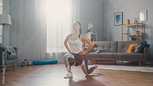 Canvas Print Strong and Beautiful Athletic Fitness Girl in Sportswear is Doing Forward Lunge Exercises in Her Bright and Spacious Living Room with Minimalistic Interior