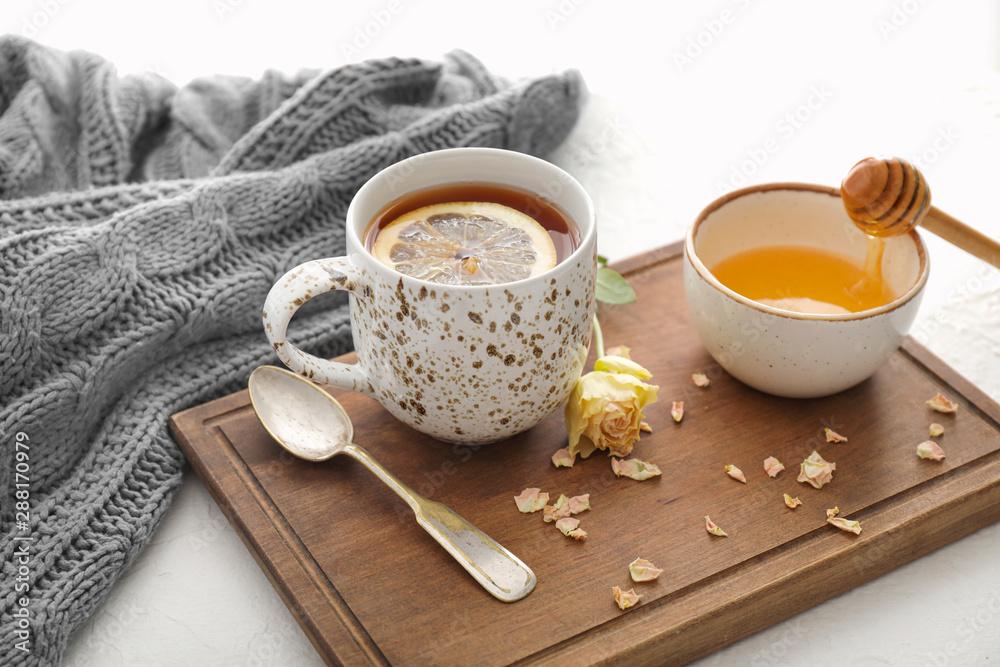 Fototapeta Cup of hot tea with lemon, honey and flower on table