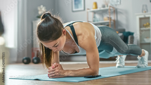 Fototapeta Strong Beautiful Fitness Girl in Athletic Workout Clothes is Doing a Plank Exercise While Using a Stopwatch on Her Phone. She is Training at Home in Her Living Room with Cozy Interior. obraz