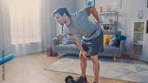 Cuadros en Lienzo Muscular Athletic Shirtless Fit Man in Grey Shorts Injures His Back After Lifting Dumbbells at Home in His Spacious and Sunny Living Room with Minimalistic Interior