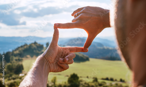 Foto auf AluDibond Dunkelbraun Rear view of Man looking at mountain landscape framing with fingers, searching for best image composition as he hiking over the mountain range. Landscape photographer or moviemaker occupation concept.