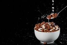 White Bowl With Assorted Cereal And Spoon With Milk Drops Isolated On Black