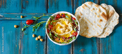 Fototapeta Hummus with olive oil, sprouts and tomatoes obraz