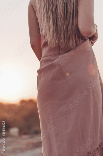 Fototapety, obrazy: body of young beautiful Caucasian blonde woman in pink dress in a deserted field on sunset background
