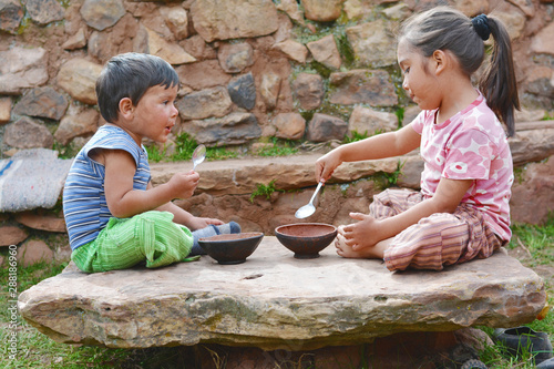 Fotografía  Little latin children sitting on the big stone and eating from rural bowl