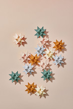 Origami Stars Made Of Paper On A Dark Beige Background With Copy Space. Creative Pattern For Christmas Card. Flat Lay