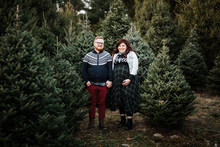 Couple Expecting Baby Posing For Christmas Card Photos