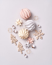 Pattern Of A Variety Of Christmas Decorations Of Paper Stars, Origami Balls And Acorns On A Gray Background. Flat Lay