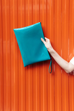 Orange Wall Background With Blue Document Case Clutch With Papers In Young Woman Hand