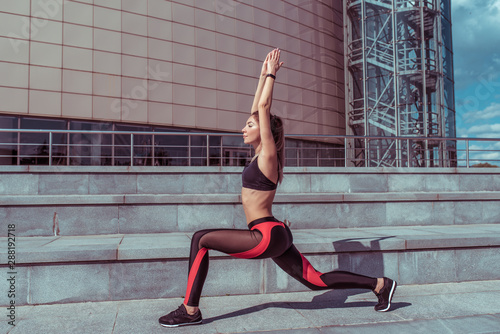 Poster Ecole de Yoga Beautiful girl athlete doing lunges exercises yoga balance concentration, summer in the city. Sportswear Leggings Top. Fitness, youth , healthy lifestyle in the city.