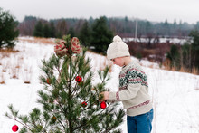Boy Decorating A Christmas Tree With Red Balls
