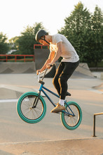 Side View Of Young Man Riding BMX Bike At Skate Park
