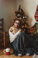 A Young Couple And Their Small Dog Decorate Their Christmas Tree
