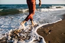 Legs Of Man Walking On Beach In Sea Wave