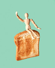 Movable Human Miniatures Model For Sketch Flying On A Toast Slice On A Light Green Background. Concept Of Healthy Food.
