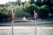 Two Twin Sisters Exercising On Parallel Bars