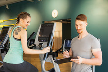 Young Woman Exercising On Step Machine In Fitness Gym With Personal Trainer Taking Notes