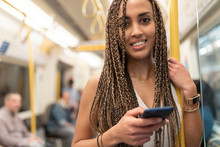 Portrait Of Smiling Young Woman With Cell Phone In Underground Train, London, UK