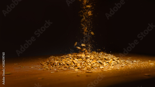 Valokuva  Oat flakes in a pile on a wooden board