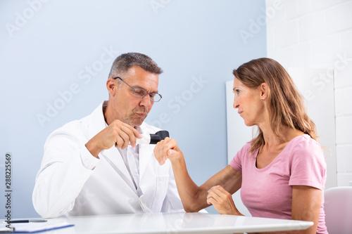 Fotografie, Obraz  Female Doctor Examining Skin Of Female Patient