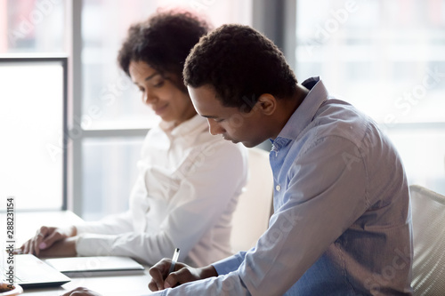Photo African American manager write assess trainee internship results