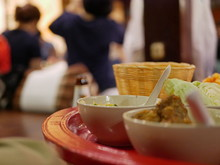 Selective Focus Of A Khantok Dinner, Northern Thai Style Meal Which People Sit And Eat On A Floor, With Blurry Background Of People At A Party