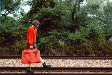 Side View Young Woman Walking On Railroad Track With Suitcase