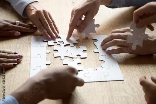 Fotografie, Tablou  Diverse people assemble jigsaw puzzle searching right decision