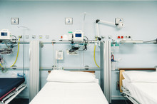 Equipped Intensive Care Unit With Beds Made Up For Patients And Metal Trays For Medical Needs